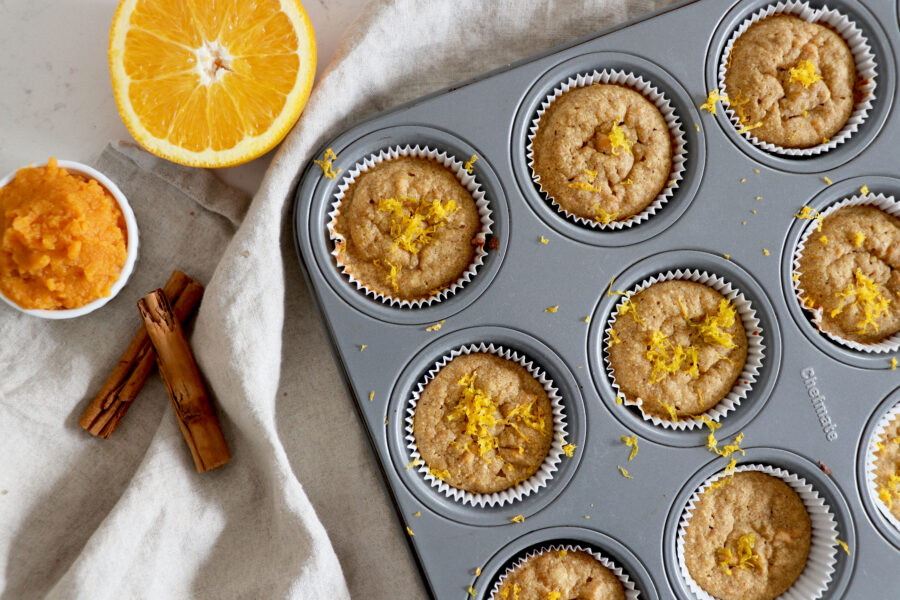 Muffin pan with orange sweet potato muffins and cinnamon sticks, orange slice and sweet potato puree on the side.