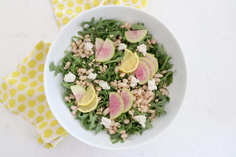 White salad bowl with lemon radish arugula salad and yellow napkin on left side.