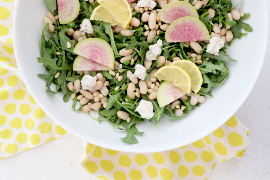 Yellow napkin with white bowl on top filled with arugula salad. Topped with pine nuts, goat cheese and sliced radishes.