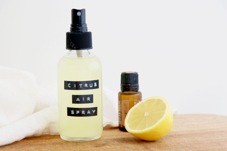 Spray bottle with citrus on wooden plank with essential oil bottle and half a lemon.