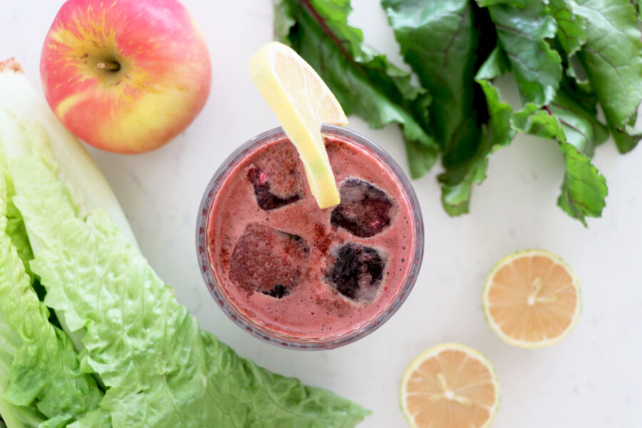 Glass of beet juice surrounded by fruits and veggies.