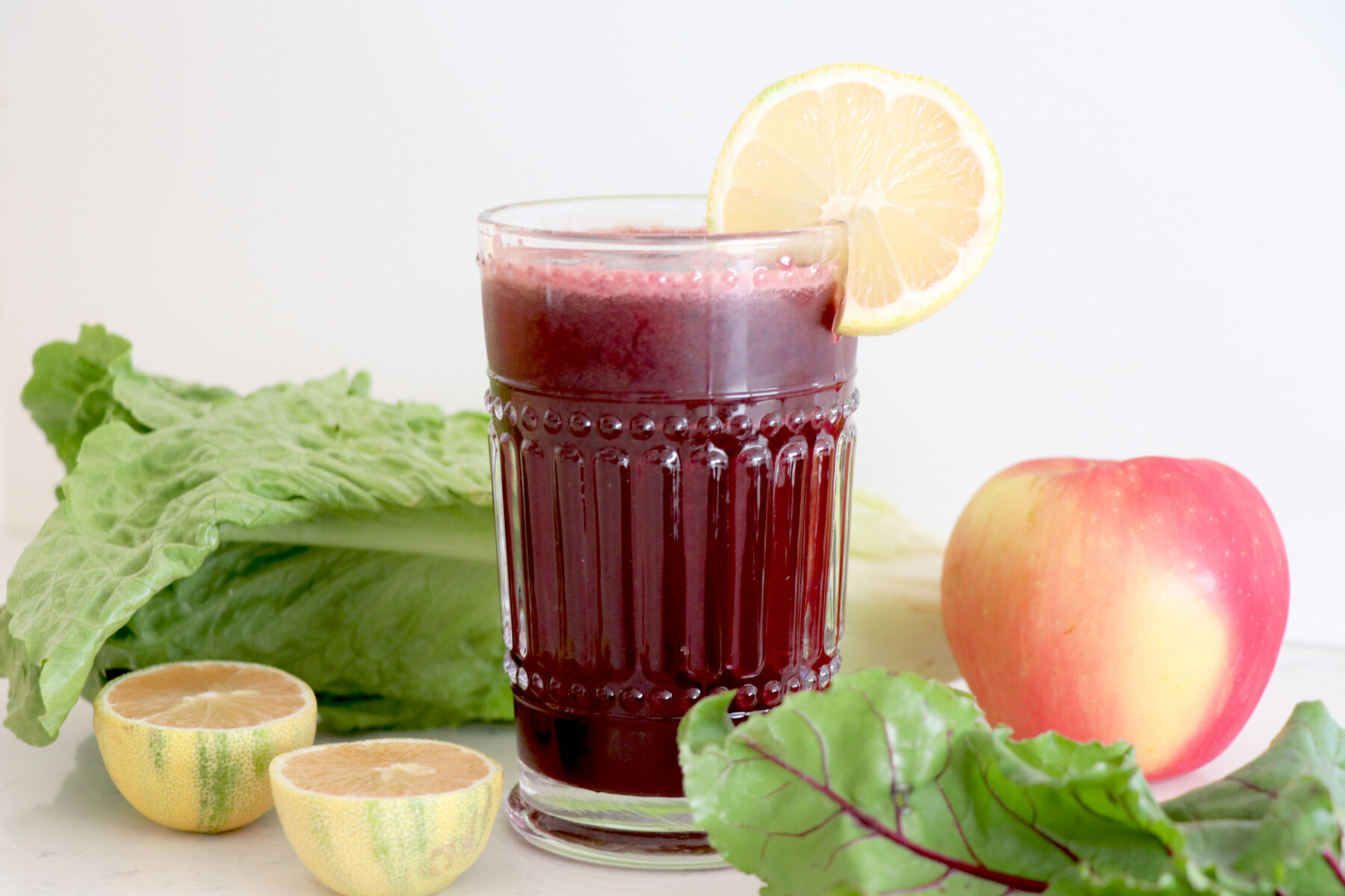 Glass with beet juice surrounded by lettuce, apple and sliced lemon.