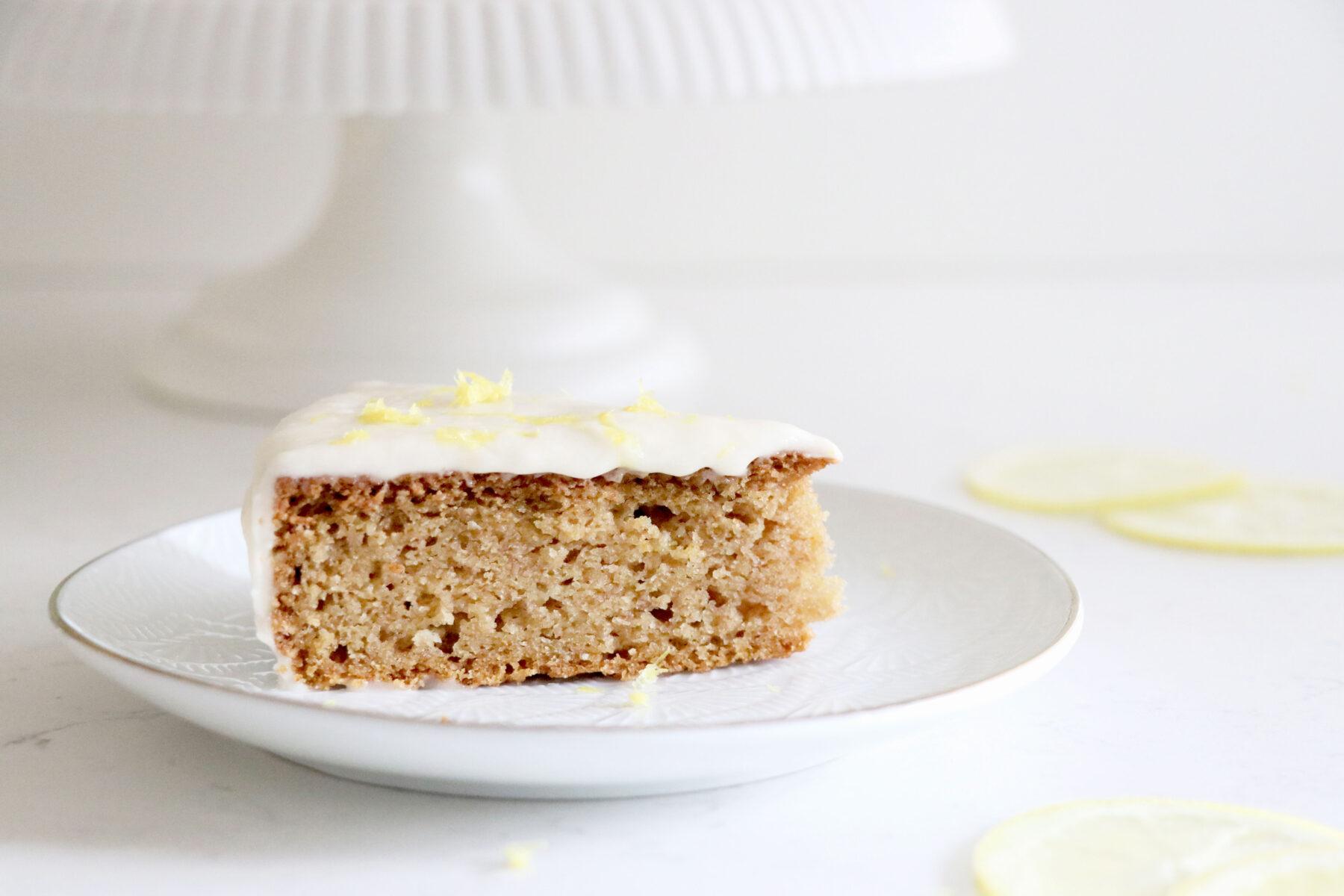 Slice of lemon cake on white plate with white cake platter in the background.