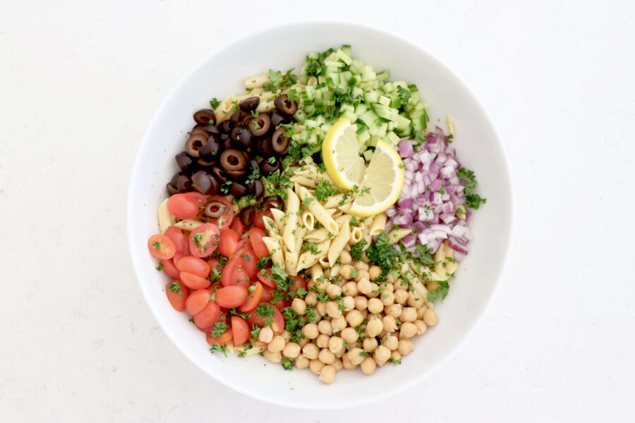 Big white bowl with pasta salad topped with diced onion, cucumber, chickpeas, olives and tomatoes.