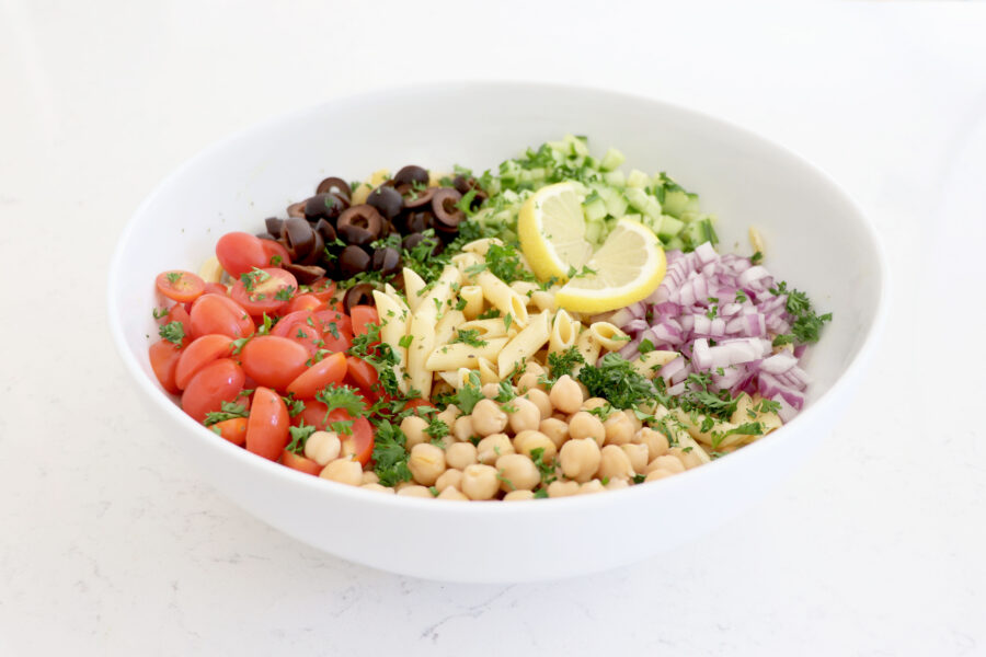 Large white bowl with pasta salad topped with veggies.