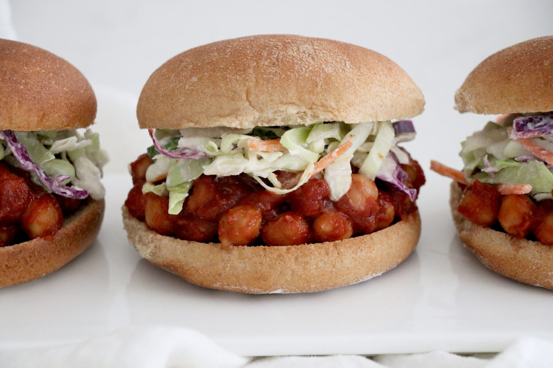 3 bbq chickpea burgers topped with coleslaw.