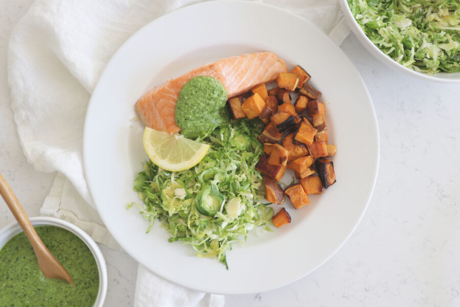 White plate with salmon, sweet potatoes and broccoli pesto.