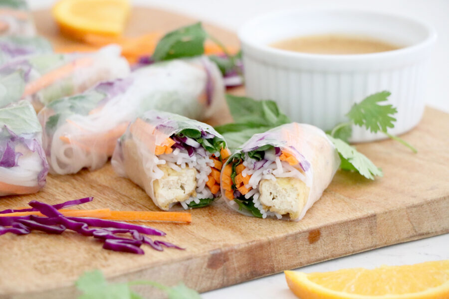 Wooden cutting board with spring rolls on top filled with veggies and a white bowl with almond pb sauce.