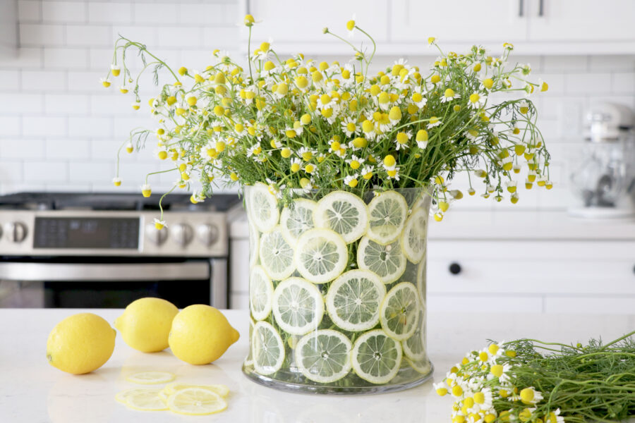 Lemon flower vase on table with flowers and lemons on the side.