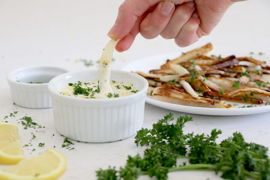 Hand dipping parsnip fries into lemon aioli sauce.