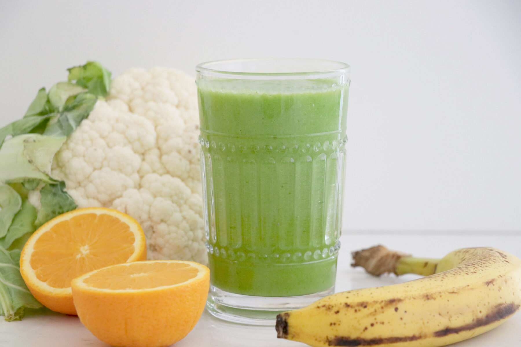 Glass filled with green smoothie surrounded by fruits and veggies.