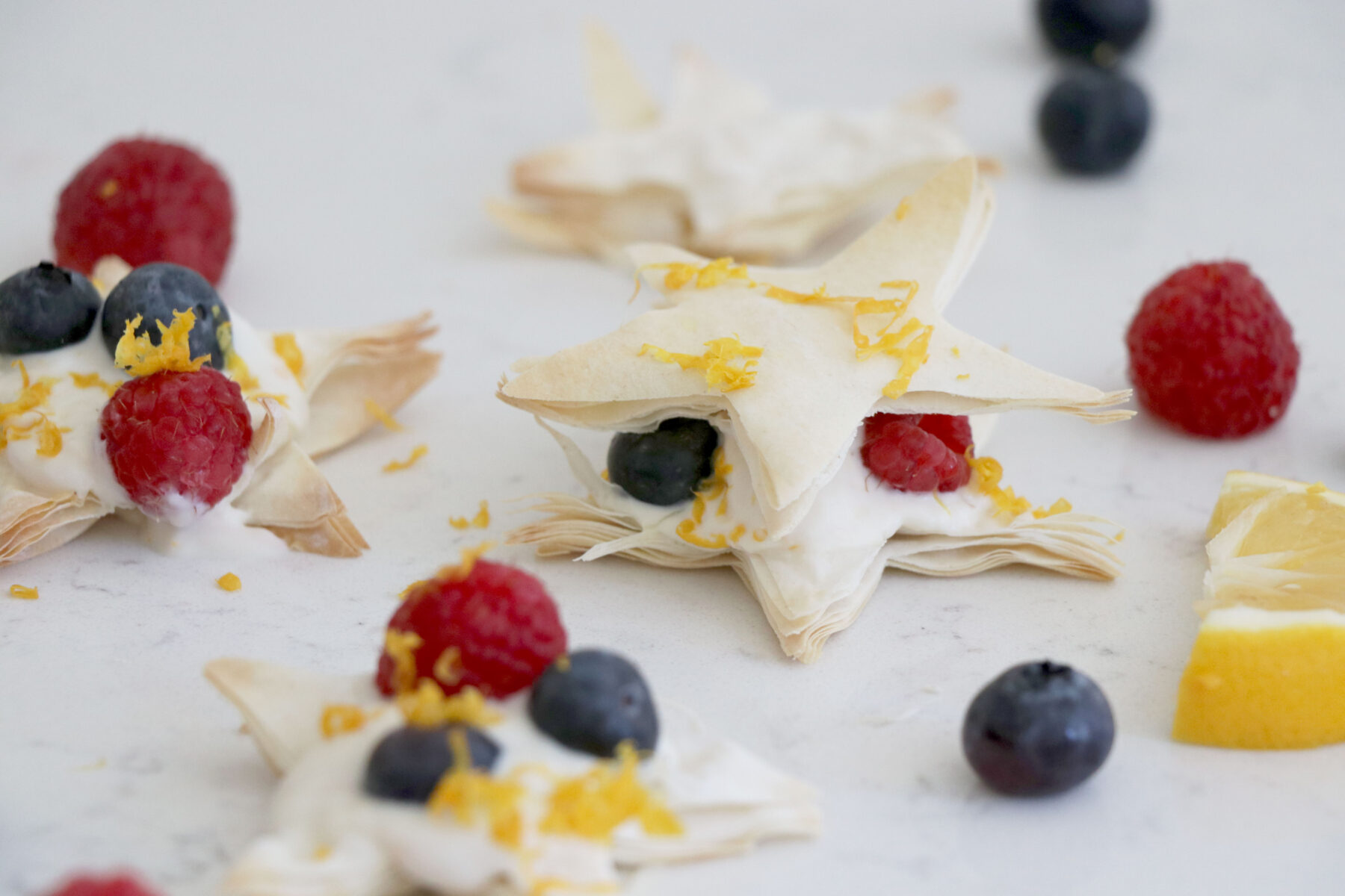 Lemon stars made from puff pastry topped with berries and lemon zest.
