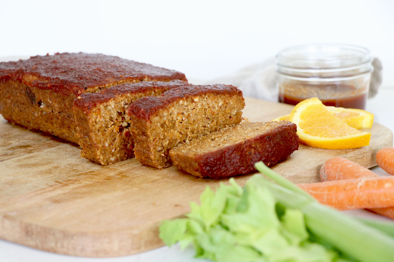 Lentil loaf cut on wooden board with celery, carrots and orange slice on the side.