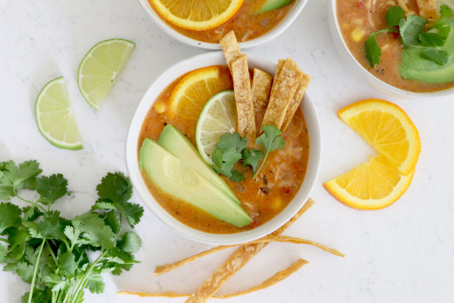 white bowls with nacho soup surrounded by veggies.