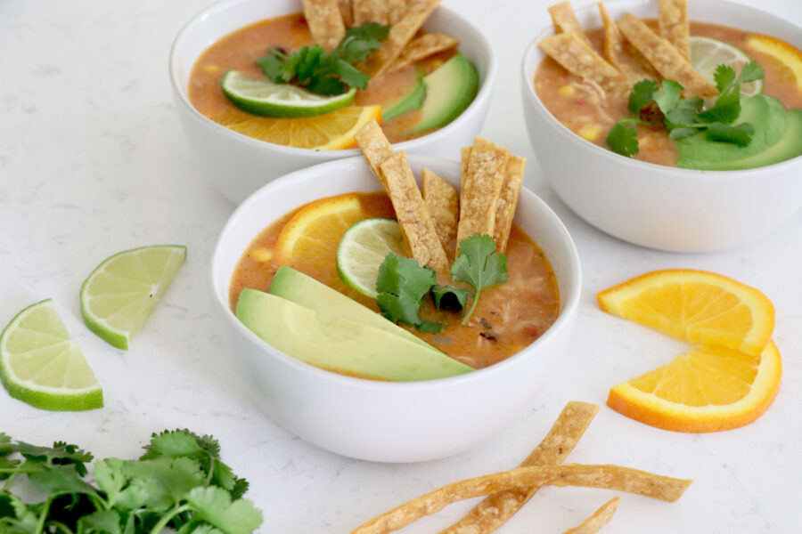 Three white bowls with nacho soup topped with tortilla strips and sliced avocado.