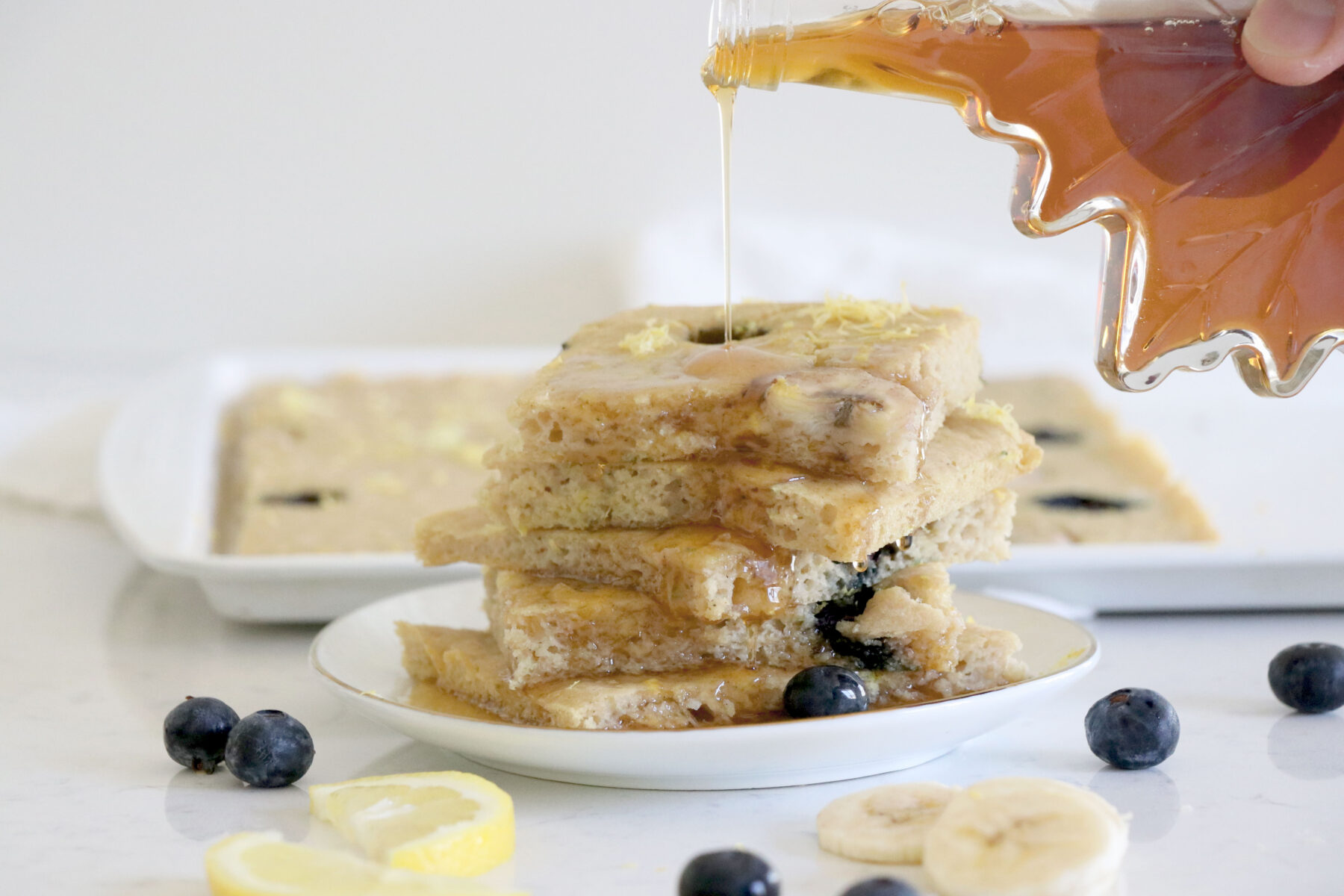 White plate with lemon blueberry pancakes and maple syrup being drizzled on top.