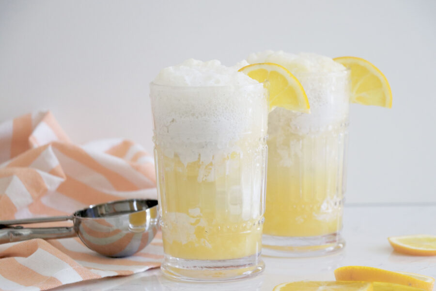 Two glasses with sparkling lemonade floats and scoop on the left side.