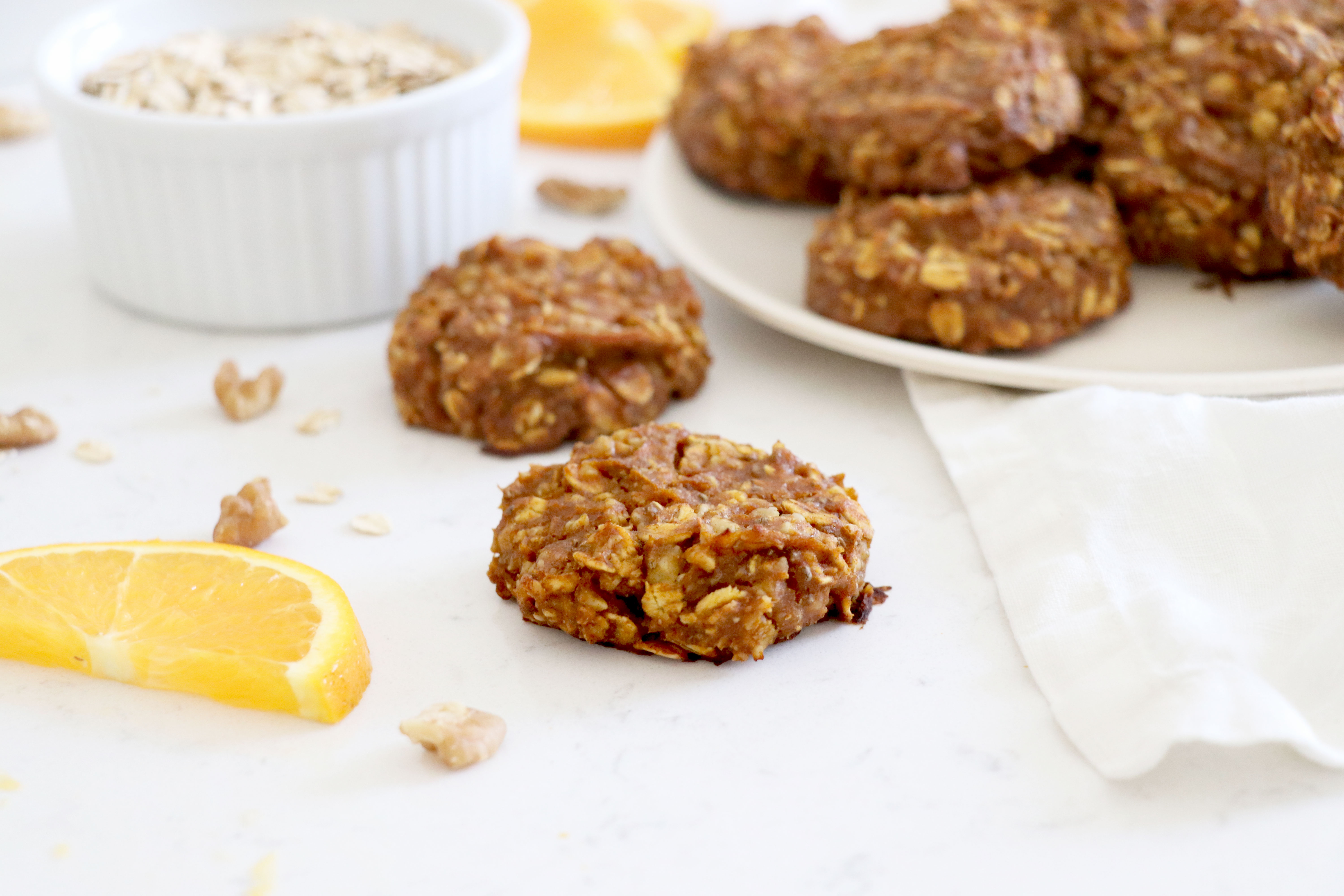 White plate of oatmeal cookies and two in the front.