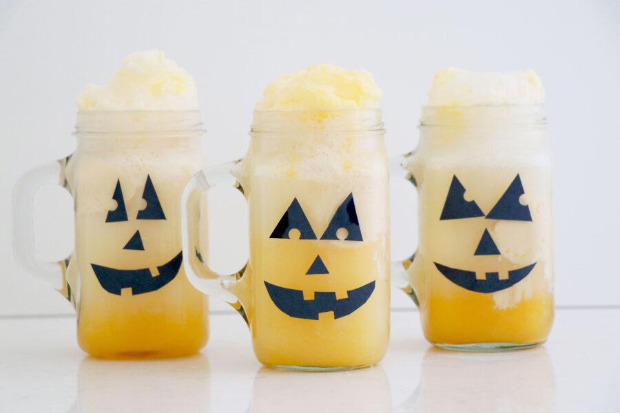 Three halloween glass jars with orange drinks.