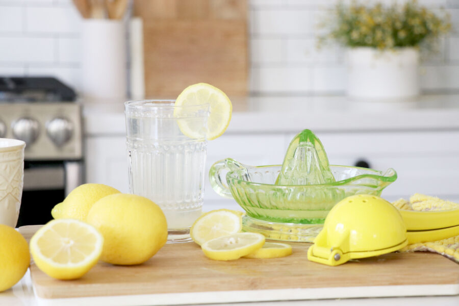 table filled with lemons, pitcher, lemon juicer and glass of lemon water.