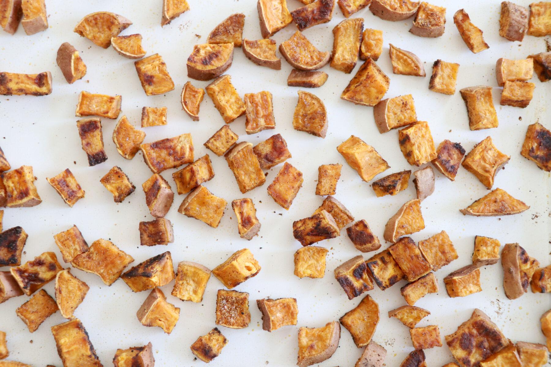 Roasted sweet potatoes on a white baking sheet