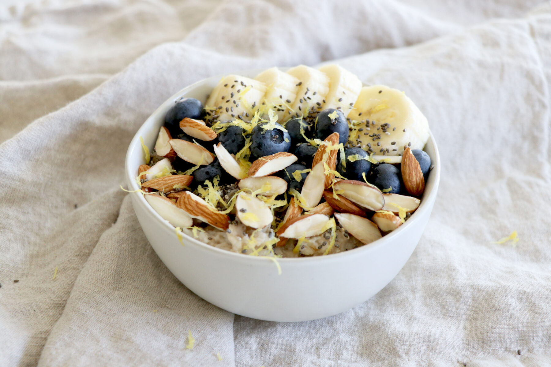 Bowl of oatmeal topped with banana, blueberries and almonds