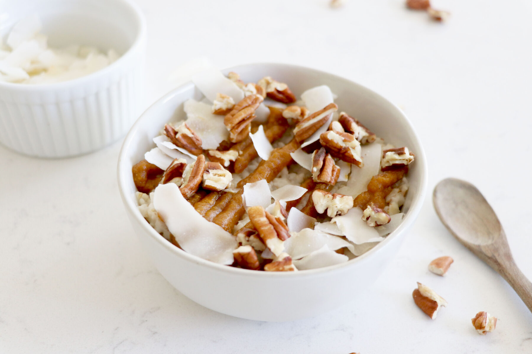 bowl of oatmeal topped with pumpkin drizzle, flaked coconut and pecans